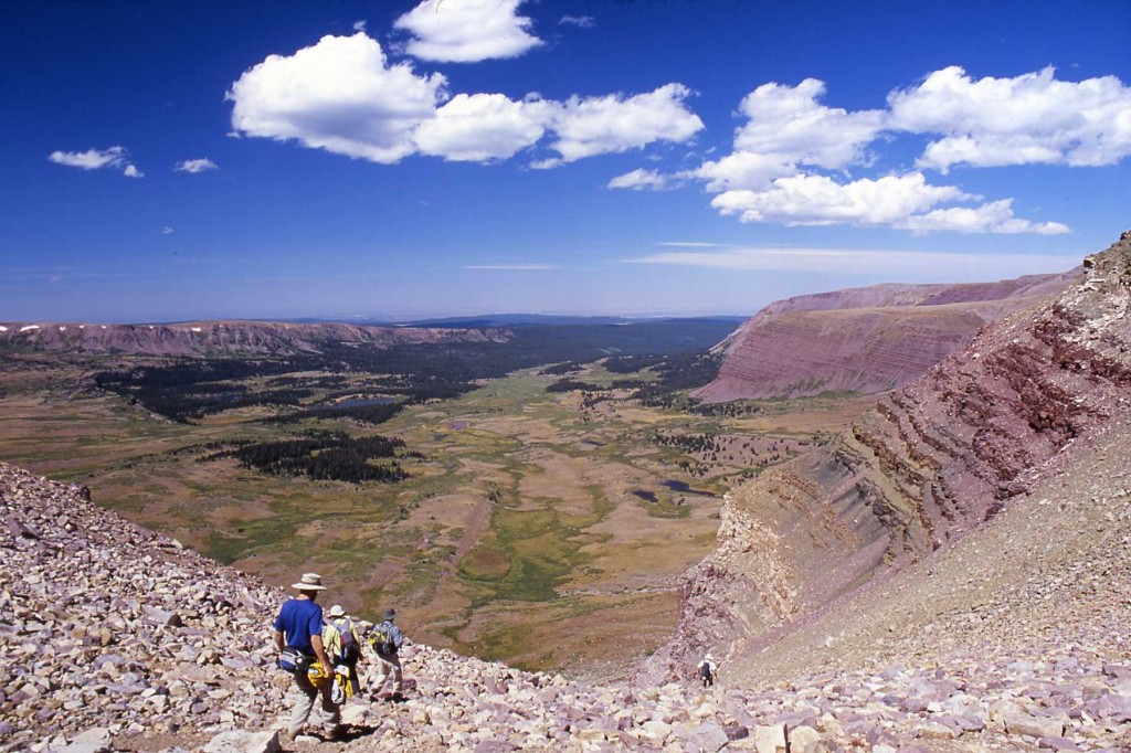 Hikers negotiate talus on interbedded sandstone, siltstone, and shale of the Uinta Mountain Group at the head of the Henrys Fork basin. Like all of the major valleys throughout the Uintas, the Henrys Fork basin was filled with ice during Pleistocene glacial episodes, the most recent being around 24,000 to 12,000 years ago.
