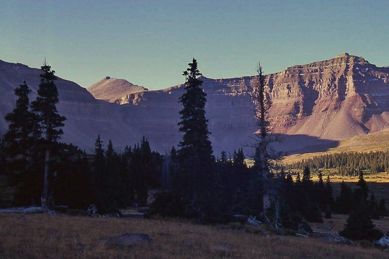 Kings Peak catches the morning sun above shadowed cliffs at the head of the Henrys Fork cirque basin in the heart of the Uinta Mountains. The layered sedimentary strata, consisting mostly of sandstone, siltstone, and shale, belong to the Precambrian Uinta Mountain Group, which underlies much of the Uinta Mountains.