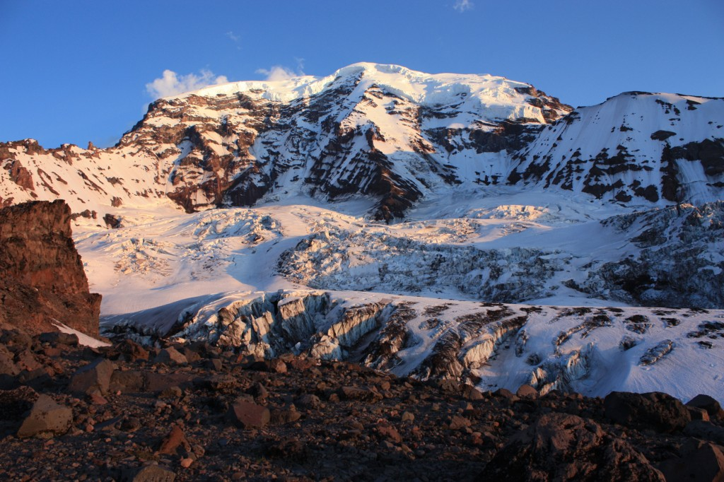 Glaciers have eroded deeply into the north face of Mount Rainier, exposing layers of lava flows in Willis Wall (left) and Liberty Wall (right) which rise precipitously over 3,000 feet (900 m) above the Carbon Glacier to Rainier's summit ice cap.