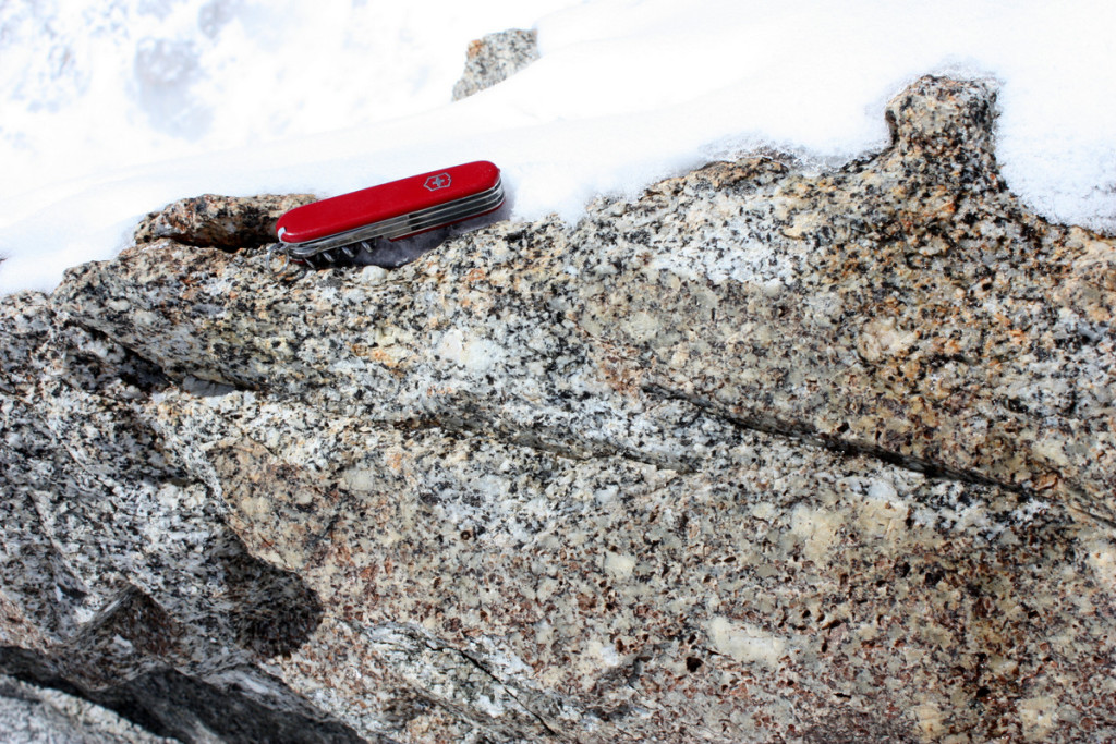 This outcrop of the 56 million-year-old McKinley Granite is adjacent to the 17,200-foot (5,200 m) High Camp on Mount McKinley's West Buttress. The intrusive igneous rock is a biotite-muscovite granite/quartz monzonite with relatively large feldspar grains (light-colored, rhomb-shaped crystals).